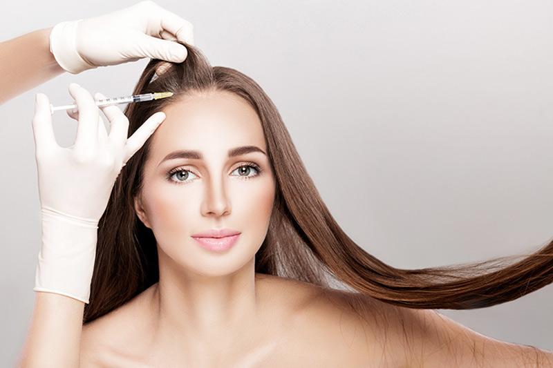 Dieses Bild zeigt eine Frau, die sich gerade in der Behandlung der Präventation von Haarausfall befindet.