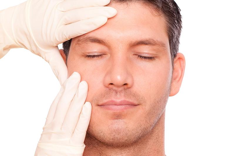 Dieses Bild zeigt einen Patienten, der gerade im Gesicht untersucht wird.